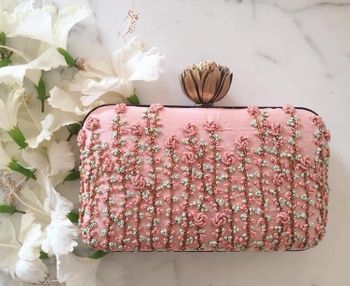 Stunning baby pink clutch with floral work and a lotus motif lock