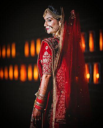 Bride in red lehenga posing for bridal portrait