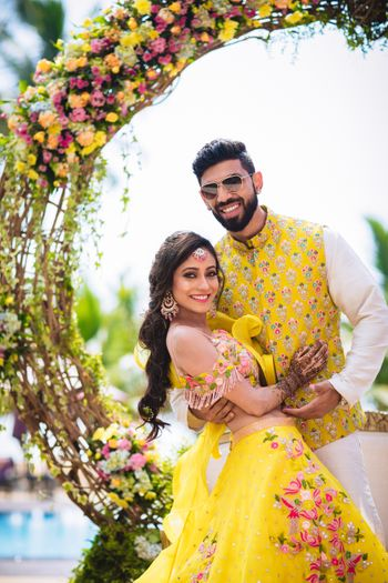 Mehendi bride and groom look in yellow outfits