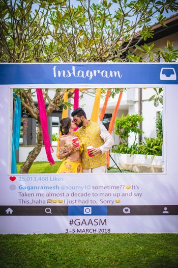 Couple kissing behind Instagram photobooth