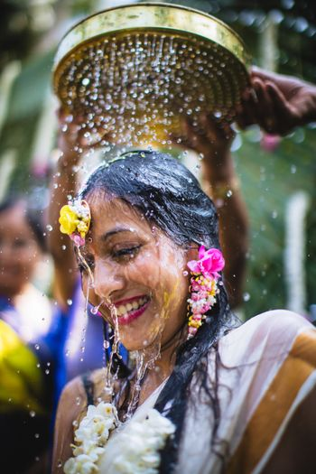 Bridal portait with water pouring on haldi