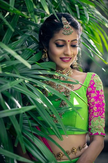 Bride in green and pink lehenga with embroidered sleeves