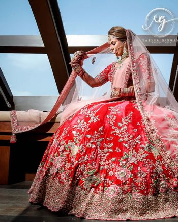 Photo of A bride in red and pink lehenga poses with a ghunghat.