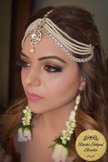 Multi-layered pearl and kundan mathapatti with floral earrings