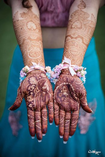 Bridal mehendi with bride and groom portraits made on it