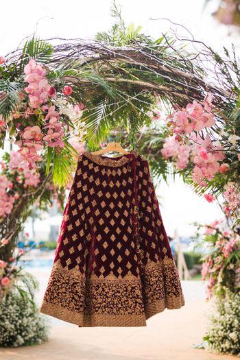Velvet lehenga on hanger with flowers