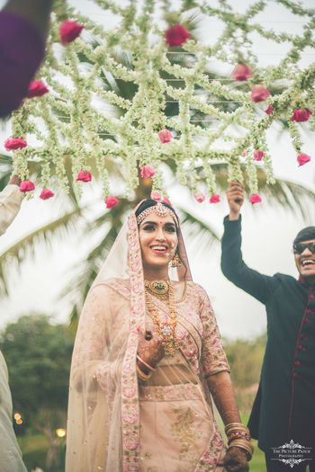Smiling bride under phoolon ki chadar