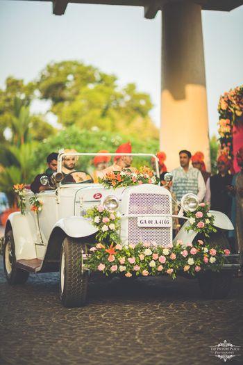 Groom entering his wedding in a vintage car