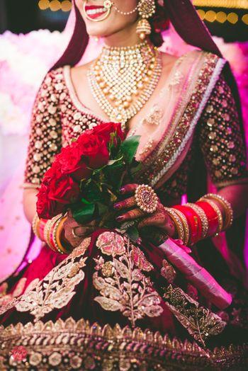 Bridal close up wearing velvet lehenga holding bouquet