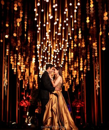 Beautiful couple shot on sangeet with gold decor