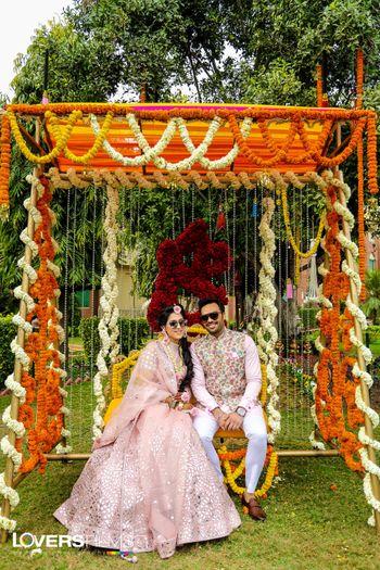 Photo of Light pink mehendi lehenga and matching groomwear