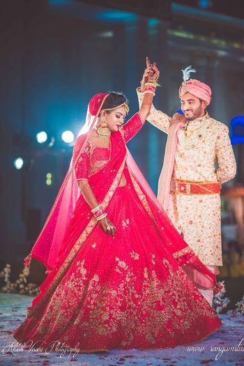 Bride twirling in red minimal bridal lehenga