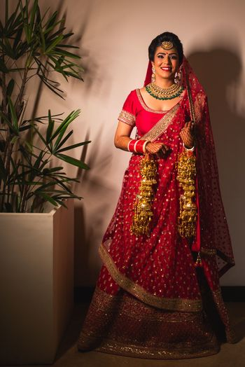 A bride in a red lehenga and gold kaleera smiles for the camera
