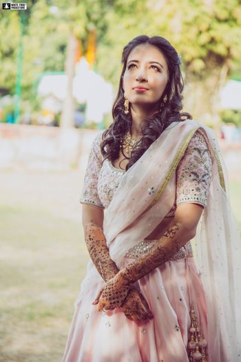 A bride in a liglht pink lehenga on her mehendi day