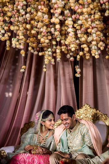 Matching bride and groom under floral string mandap