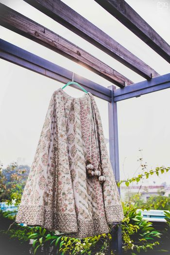 Photo of A shot of a white lehenga handing from a hanger