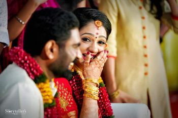 A south indian bride laughs as she looks at her husband