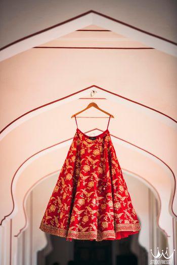 Red and gold Sabyasachi bridal lehenga on hanger