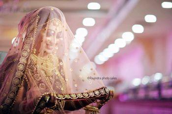 A sikh bride takes her dupatta as a veil