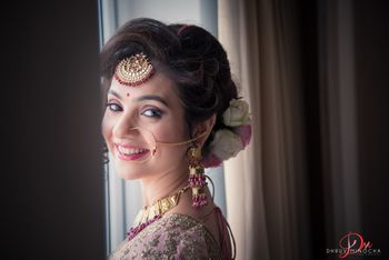 A bride smiles as she gets ready, wearing a maang tika and a floral bun