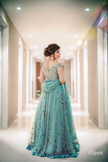 A stunning look of a bride in an off-shoulder blue lehenga.