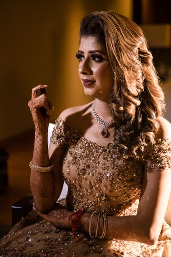 A bride to be sits pretty in a gold gown