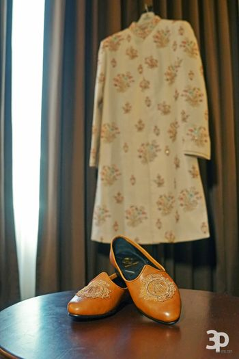 Groom shoes and sherwani on hanger