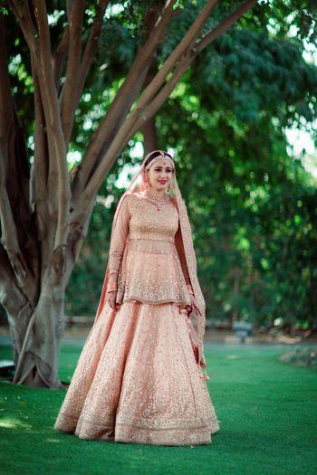 Photo of Peach bridal lehenga with peplum blouse