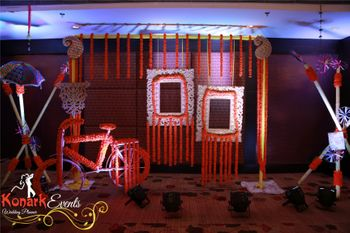 Pretty floral photobooth with hanging frames and bicycle for mehendi