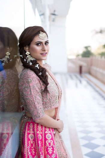 Photo of Mehendi side braid with flowers and benarasi lehenga