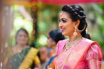 south indian bridal look in pink kanjivaram with twist hairdo