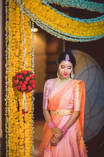 south indian bride in orange kanjivaram and gold waistbelt