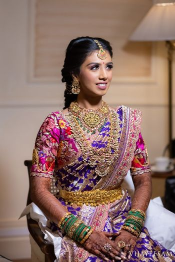 South Indian bride wearing an aubergine and gold saree with a multi-coloured blouse.