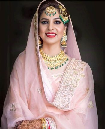 Bride in light pink outfit with gold jewellery