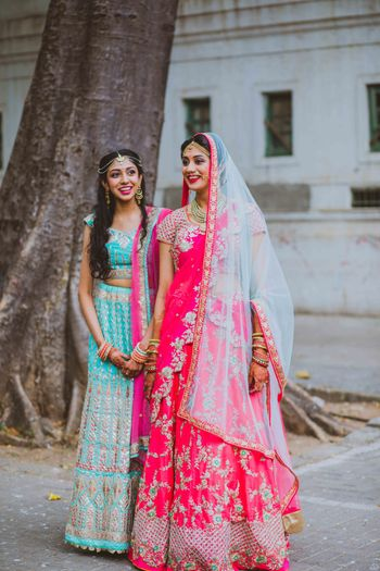 Bride with sister in bright lehengas