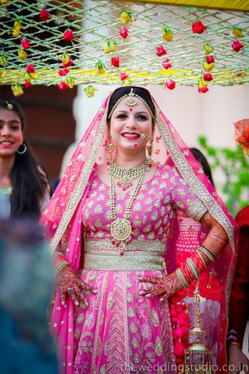 Bride entering in bright pink lehenga