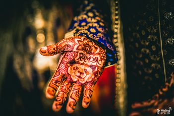 Groom wearing mehendi with brides name and a panda