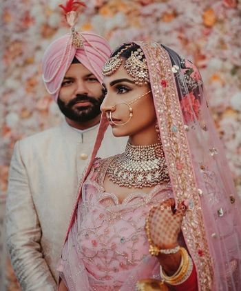 Photo of Couple portrait with bride in light pink lehenga and pretty jewellery