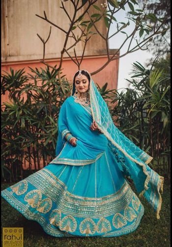 Bride twirling in light blue lehenga.