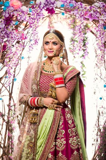 Gorgeous bride in magenta bridal lehenga with kundan and emerald jewelry