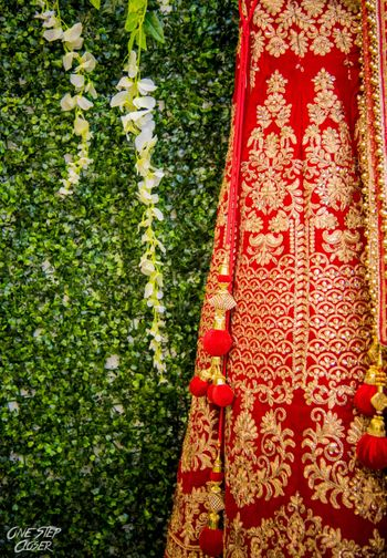 Red and gold bridal lehenga with tassels