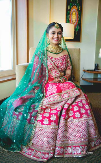 Off shoulder blouse with red and green lehenga