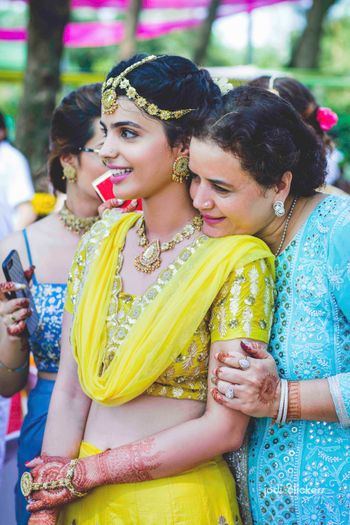 Bride with mom on mehendi in yellow lehenga