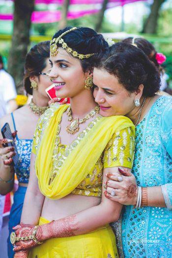 Photo of Bride with mom on mehendi in yellow lehenga