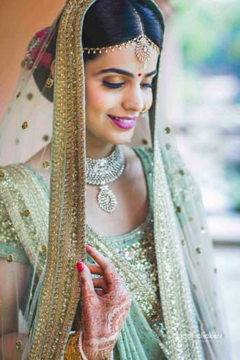 Photo of Bridal portrait with offbeat colour lehenga and red bun
