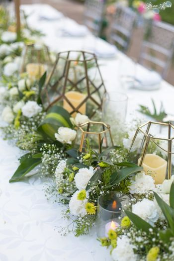 Long table centrepiece setting with candles and florals