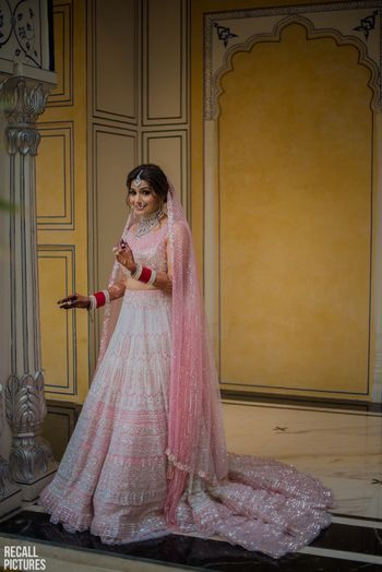 Light pink and white bridal lehenga with train