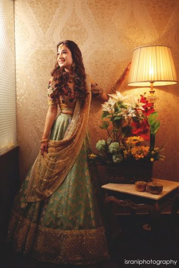 Bride in hotel room in green lehenga