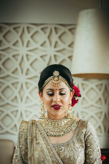Contrasting makeup and bridal bun in red with gold lehenga