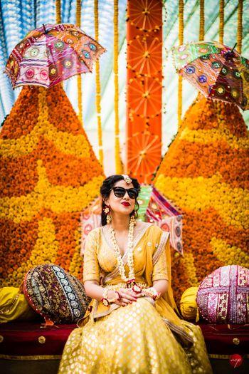 Happy bride shot in yellow lehenga on mehendi
